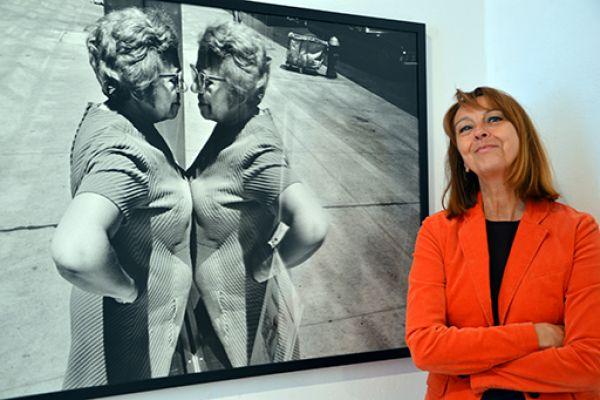 """Die Leiterin des KuK Monschau, Frau Dr. Nina Mika-Helfmeier, neben dem Foto von Richard Kalvar """"Woman looking at herself in store window, New York City, 1969"""""""